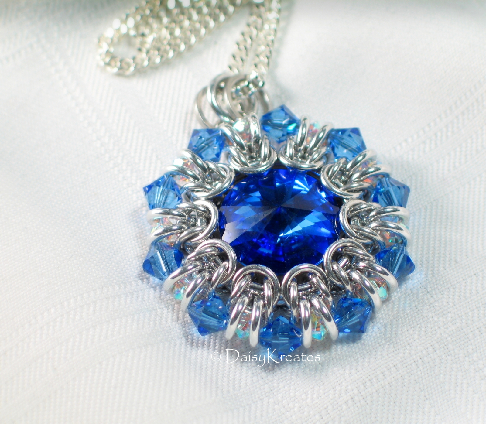 Helios sunburst medallion pendant with jewel tone swarovski clear and blue bicone beads form pointy outer rim as crystal ruffle aloadofball Choice Image